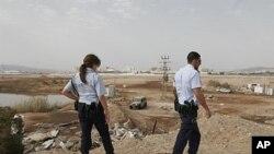 دوو پـۆلیسی ئیسرائیلی سهیری ئهو شوێنه دهکهن که یهک له ڕۆکێتهکانی لێـکهوتووه، شـاری ئیلات، دووشهممه 2 ی ههشتی 2010