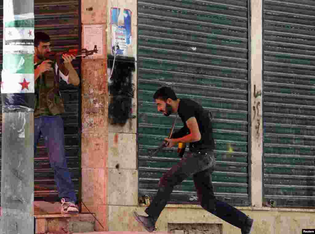 8月5日,在阿勒颇城萨拉赫丁区的战火中,一名反政府的叙利亚自由军寻求掩护躲避政府军的 炮轰