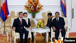 Chinese Foreign Minister Wang Yi (L) meets with Cambodia's Prime Minister Hun Sen in Phnom Penh, August 21, 2013.