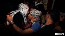 Warga Palestina Rami Barbakh, yang ditahan Israel selama 20 tahun, memeluk ibunya setiba di Khan Younis, Jalur Gaza setelah dibebaskan Israel Selasa (31/12).