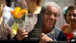 Un admirador del Gabo sostiene un ejemplar de la biografía del escritor y una flor amarilla frente al Palacio de Bellas Artes.