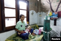 FILE - A refugee from Myanmar sits with her sick child at the Mae Tao clinic in the bordering town of Mae Sot, Oct. 30, 2015. Migrants have mixed emotions over Myanmar's election - hope that a hated government will be defeated, and fear of the uncertain future such an upheaval might bring.