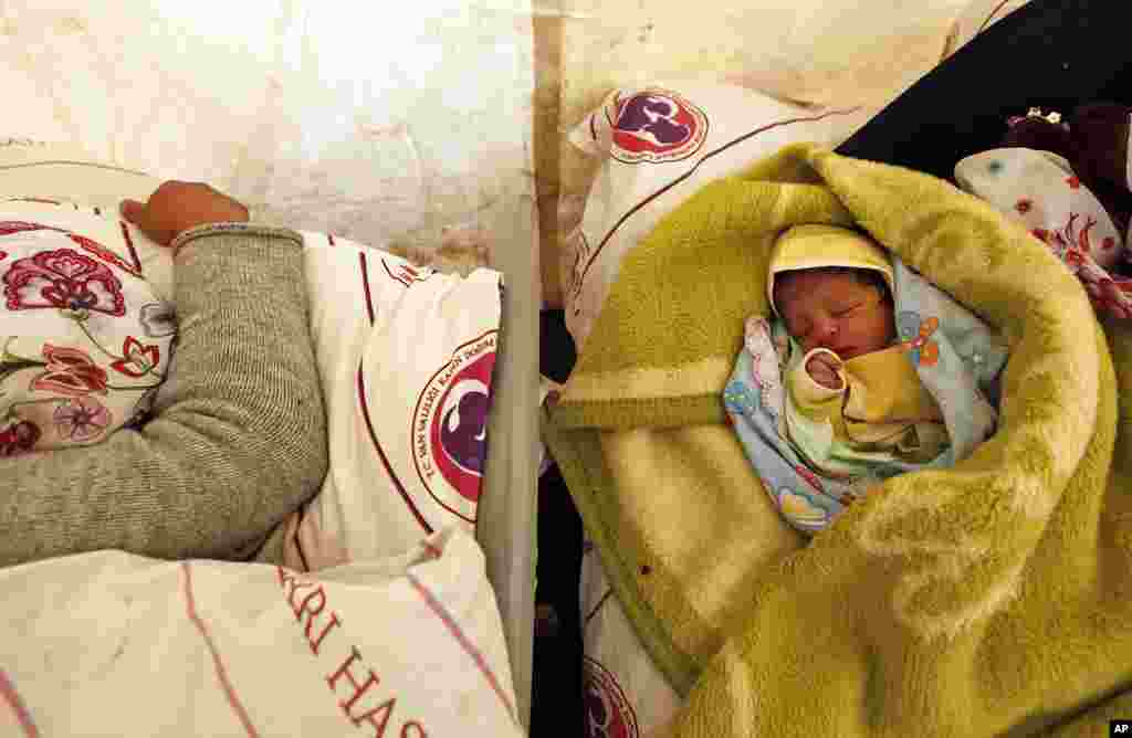 Today born baby Gurbet sleeps next to his mother Fezile Sonmez, 21, in a tent at an improvised maternity ward outside a canteen in Van, October 25, 2011. (Reuters)