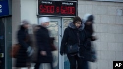 People walk past electronic display board with figures indicating US dollar to Russian ruble currency exchange rate, St. Petersburg, Russia, Dec. 29, 2014.