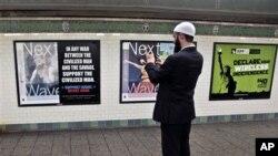 Sayrus MakGoldrik metro bekatidagi plakatni suratga olmoqda