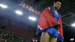 15일 브라질 리우올림픽 남자 기계체조 도마에서 금메달을 차지한 북한 리세광 선수가 우승이 확정된 후 북한 국기인 인공기를 몸에 두르고 있다.