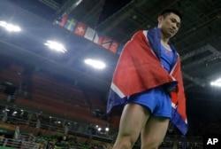 15일 브라질 리우올림픽 남자 기계체조 도마에서 금메달을 차지한 북한 리세광이 우승이 확정된 후 북한 국기인 인공기를 몸에 두르고 있다.