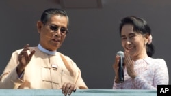 Leader of Myanmar's National League for Democracy party, Aung San Suu Kyi, delivers a speech with party patron Tin Oo from a balcony of her party's headquarters in Yangon, Myanmar, Nov. 9, 2015.