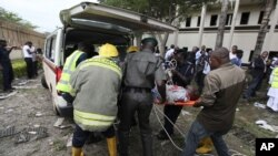 A victim of a bomb blast ripped through the United Nations offices in the Nigerian capital of Abuja is loaded into an ambulance, after a car rammed into the building, and witnesses said they had seen a number of dead bodies being carried from the site.