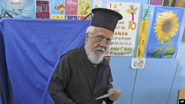 A Greek Orthodox priest holds his ballot paper as he exits a voting booth at an Athens primary school used as a polling station, during Greece's general election, May 6, 2012.