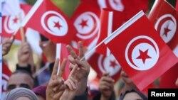 Des Tunisiens agitent des drapeaux lors d'une manifestation à Tunis le 14 février 2018