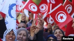 People wave national flags during demonstrations on the seventh anniversary of the toppling of president Zine El-Abidine Ben Ali, in Tunis, Jan. 14, 2018.