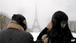 在法国巴黎下雪后,人们在艾菲尔铁塔附近拍照