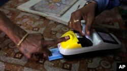 FILE - A woman places her finger on a biometric card reader before buying her quota of subsidized rice from a fair price shop under the Public Distribution System in Rayagada, in the Indian eastern state of Orissa, March 20, 2012.