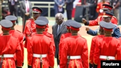 Kenya's outgoing President Mwai Kibaki inspects the honor guard before the official swearing-in ceremony of President Uhuru Kenyatta at Kasarani Stadium, Nairobi, April 9, 2013.