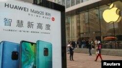 在中国上海的Apple商店外面,顾客排队购买新的iPhone XR手机,附近有华为Mate 20系列产品的广告。(2018年10月26日)