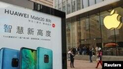 2018年10月26日在中国上海的Apple商店外面,顾客排队购买新的iPhone XR手机,附近有华为Mate 20系列产品的广告。