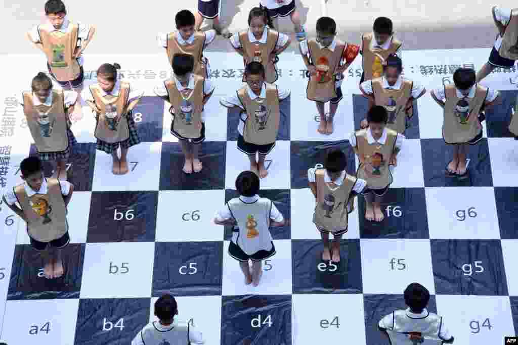 """河北省邯郸市农林路小学的学生比赛""""真人国际象棋""""(2017年6月19日),装扮成""""王、后、车、象、马、兵""""的""""棋子"""",在大型棋盘上变幻队列。"""