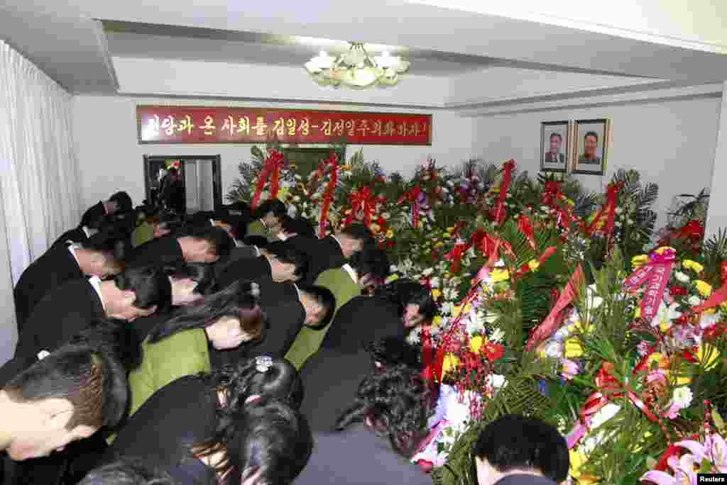 North Koreans present wreaths and bow in front of portraits of Kim Il Sung and Kim Jong Il as they mourn the second death anniversary of Kim Jong Il at the North Korean embassy in the Chinese border city of Dandong, Dec. 17, 2013.