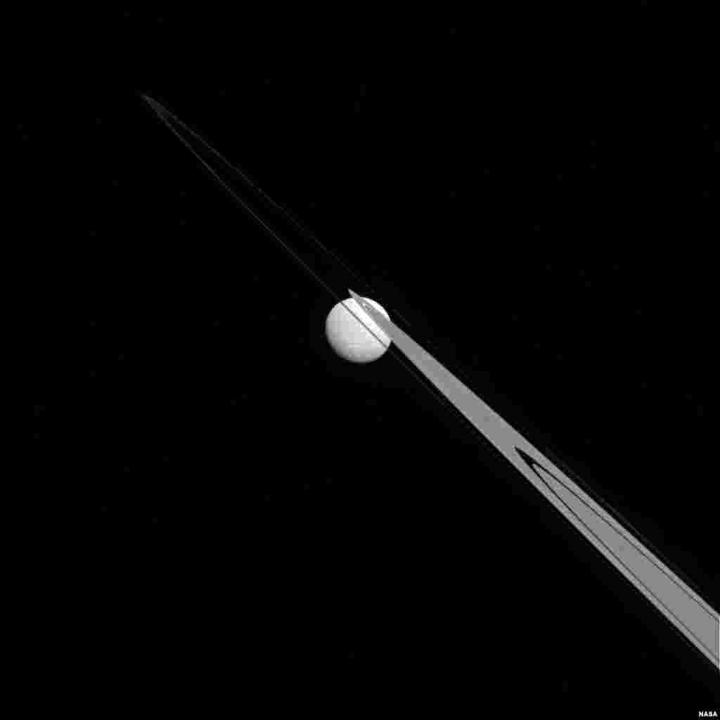 Like a drop of dew hanging on a leaf, Tethys appears to be stuck to the A and F rings from this perspective. Tethys (660 miles, or 1,062 kilometers across), like the ring particles, is composed primarily of ice. (Credit: NASA/JPL-Caltech/Space Science Institute)