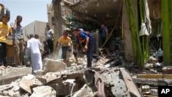 Warga setempat memeriksa lokasi ledakan pasca serangan bom mobil di wilayah al-Ameen, Baghdad, Irak (8/6). Dua ledakan dan satu penyerang bunuh diri kembali mengguncang Irak, di pasar makanan kota Jadida al-Shat, sekitar 40 kilometer utara Baghdad, Senin (10/6).