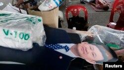 Boneka karton mantan perdana menteri Thailand Thaksin Shinawatra dekat jenazah seorang pria yang tewas dalam demonstrasi anti-pemerintah di Bangkok (1/12).