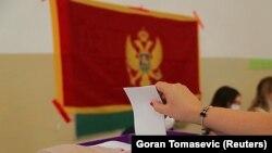 Seorang perempuan memasukkan surat suara dalam pemilihan legislatif, di Podgorica, Montenegro, 30 Agustus 2020.