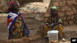 Village girls watch from a broken wall as local health workers remove earth contaminated by lead from a family compound in the village of Dareta in Gusau, Nigeria, June 10, 2010.
