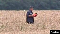 격추된 말레이시아 항공기의 비행기록장치로 보이는 물건을 구조대원이 들고가는 모습. 지난 18일에 촬영된 동영상에 담긴 장면이다.