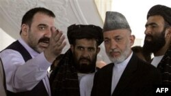 Na arhivskom snimku iz oktobra 2010, avganistanski predsednik Hamid Karzai razgovara sa svojim polubratom Amadom Valijem Karzaijem u pokrajini Kandahar.