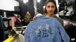 "Palestinian-American Yasmeen Mjalli displays a jacket with the slogan ""Not Your Habibti (darling),"" as a ready-made retort for cat calls, in the West Bank city of Ramallah, Jan. 24, 2018. The 21-year-old is the driving force behind a nascent #MeToo movement in the West Bank, selling her line of T-shirts, hoodies and denim jackets, to encourage Palestinian society to confront sexual harassment, a largely taboo subject."