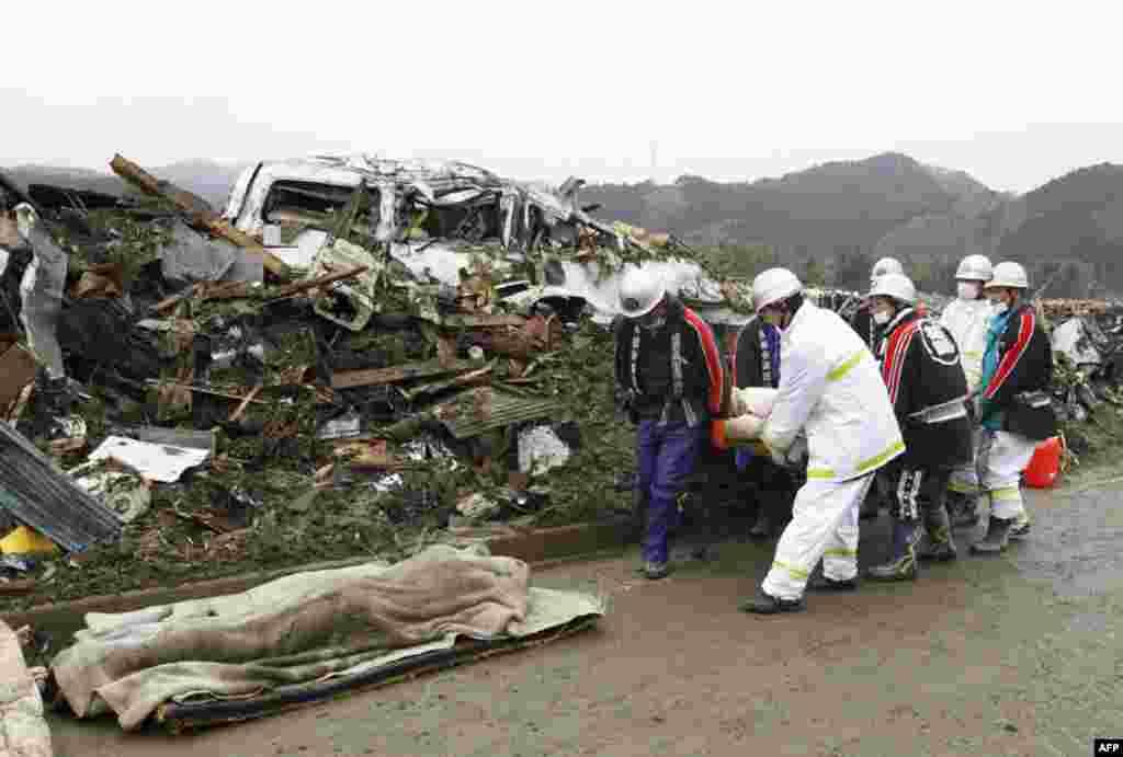 Спасатели несут тело жертвы пострадавшей в результате разрушений землетрясением и цунами, Япония, 15 марта 2011г.
