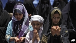 Yemeni children, chant prayers with female anti-government protesters, during a demonstration demanding the resignation of Yemeni President Ali Abdullah Saleh, in Sana'a, Yemen, May 19, 2011.