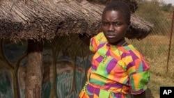 Nighti Aparo akisimama nje ya nyumbani kwao kaskazini mwa Uganda.