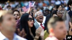 Alfonso Perez, of the Dominican Republic, cheers at the start of a naturalization ceremony for 755 new United States citizens at Turner Field, home of the Atlanta Braves baseball team in Atlanta, Sept. 16, 2016.