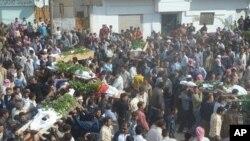 ພວກປະທ້ວງຕໍ່ຕ້ານລັດຖະບານຫາມຫີບສົນຂອງພວກຊາວບ້ານ ມຸສລິມນິການຊຸນນີທີ່ໄດ້ເສຍຊິວິດໄປໃນເຂດ ນຶ່ງໃກ້ກັບເມືອງ Homs, ຊີເຣຍ. ວັນທີ 3 ພະຈິກ 2011.
