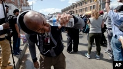 Un manifestante se limpia el rostro tras ser afectado por gas lacrimógeno durante una protesta en Baltimore.