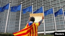FILE - Catalan Raimon Castellvi wears a flag with an Estelada (Catalan separatist flag) as he protests outside the European Commission in Brussels after Sunday's independence referendum in Catalonia, Belgium, Oct. 2, 2017.