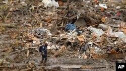Rescue worker traverses massive debris pile at scene of deadly mudslide, Oso, Wash., March 27, 2014.