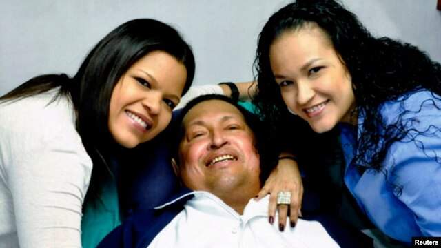 Venezuela's President Hugo Chavez smiles in between his daughters, Rosa Virginia (R) and Maria while recovering from cancer surgery in Havana in this photograph released by the Ministry of Information on Feb. 15, 2013.