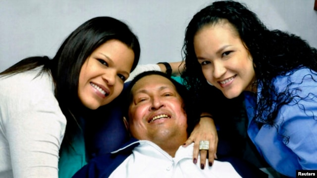 Venezuela's President Hugo Chavez smiles in between his daughters, Rosa Virginia (R) and Maria while recovering from cancer surgery in Havana in this photograph released by the Ministry of Information on February 15, 2013.