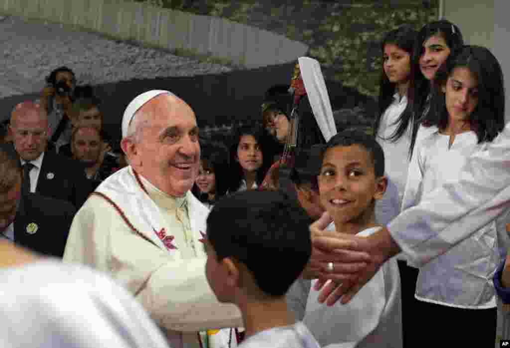 Pope Francis shakes hands with children from nearby Palestinian refugee camps who came to welcome him at the Dheisheh camp near Bethlehem, West Bank, May 25, 2014.