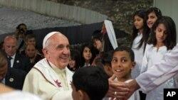 Paus Fransiskus bersalaman dengan anak-anak pengungsi Palestina di kamp Dheisheh dekat Bethlehem, Tepi Barat (25/5). (AP/Menahem Kahana)
