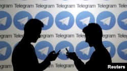 FILE - Two men pose with smartphones in front of a screen showing the Telegram logos in this picture illustration taken Nov. 18, 2015.
