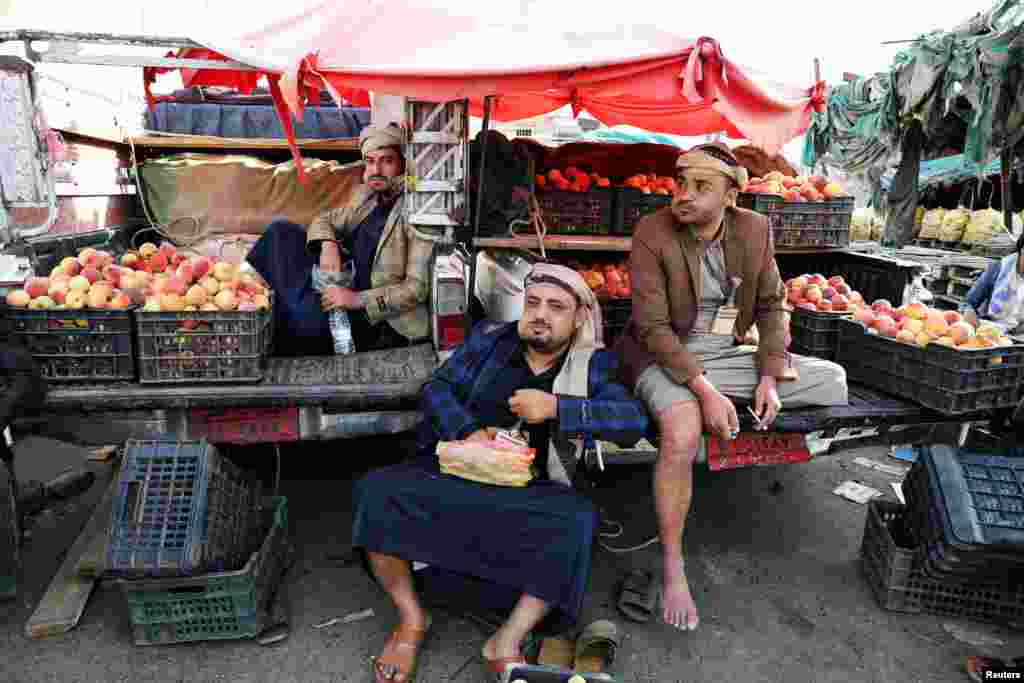 Fruit vendors chew qat, a mild stimulant at a fruit market in Sana'a, Yemen.