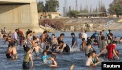 រូបឯកសារ៖ មនុស្សនាំគ្នាហែលទឹកនៅទន្លេ Euphrates ក្នងុពេលអាកាសធាតុក្ដៅ នៅទីក្រុង Raqqa ប្រទេសស៊ីរី កាលពីខែឧសភា ២០១៩។