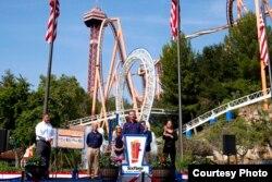 California Governor Gavin Newsom (center) welcomes visitors to the Six Flags Magic Mountain theme park in California, June 16, 2021 (doc: David Crane/The Orange County Register via AP)