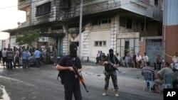 Des membres de la garde de sécurité du Hamas devant un immeuble touché par un explosif à Gaza, 19 juillet 2015.