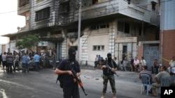 Anggota Hamas berjaga-jaga dekat sebuah kendaraan yang hancur akibat ledakan di kota Gaza, Minggu, 19 Juli 2015.