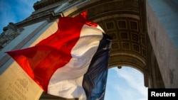 រូបភាពឯកសារ៖ ទង់ជាតិបារាំងបក់នៅក្រោម Arc de Triomphe អំឡុងពិធីរំឮកថ្ងៃបញ្ចប់សង្រ្គាមលោកលើកទី០១ កាលពីថ្ងៃទី១១ ខែវិច្ឆិកា ឆ្នាំ២០១៣។